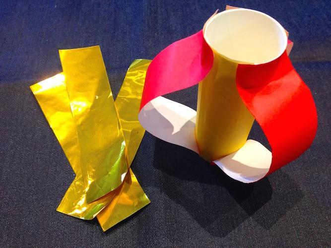 トイレットペーパーの芯の上下部分に折り紙をたわませる様に貼り付ける様子