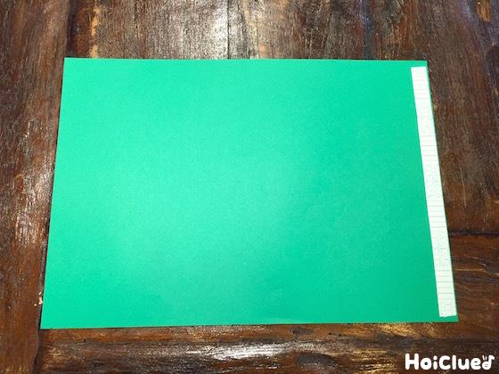 緑の画用紙の片端に両面テープを貼った写真