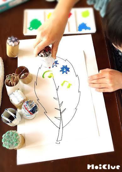 1枚の大きな葉の絵を描いた画用紙にスタンプする様子