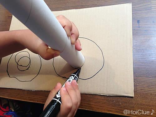 ダンボールに丸を描いている写真