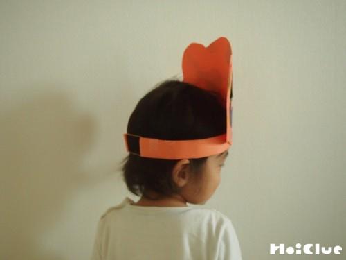 完成したおばけかぼちゃの冠をかぶる子どもの写真