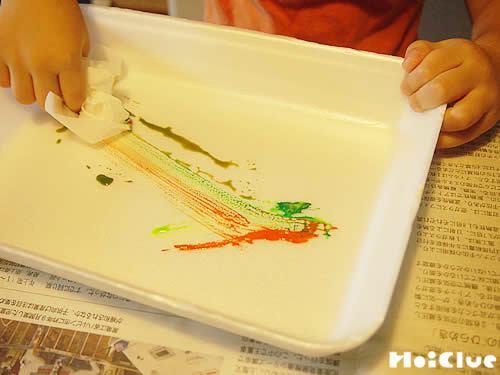 丸めた花紙に絵の具をつける子どもの様子