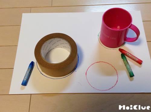 画用紙の上にコップやガムテープを置き、なぞって丸を描く様子